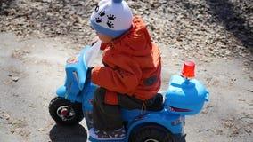 Een gelukkig kind die een elektrische auto berijden stock video