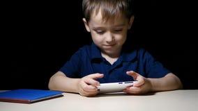 Een gelukkig kind die gelukkig op een beeldverhaal letten bij nacht die een smartphone en het glimlachen gebruiken stock video