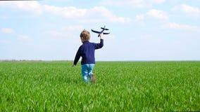 Een gelukkig kind houdt een stuk speelgoed vliegtuig in zijn hand, loopt langs het groene gazon in langzame motie stock footage