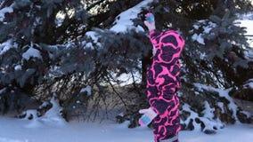 Een gelukkig kind in een jumpsuit speelt met sneeuw dalende bomen stock video