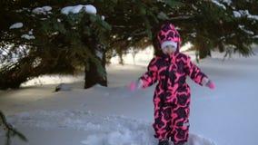Een gelukkig kind in een jumpsuit speelt met sneeuw dalende bomen, langzame motie stock videobeelden