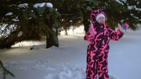 Een gelukkig kind in een jumpsuit speelt met sneeuw dalende bomen, langzame motie stock footage