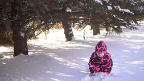 Een gelukkig kind in een jumpsuit speelt met sneeuw, langzame motie stock videobeelden
