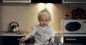 Een gelukkig kind zit op een lijst en speelt met een metaalgietlepel stock footage