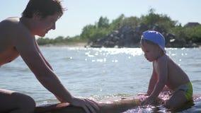 Een gelukkig kind zwemt in het overzees Pret en spelen in openlucht stock footage