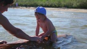 Een gelukkig kind zwemt in het overzees Pret en spelen in openlucht stock videobeelden