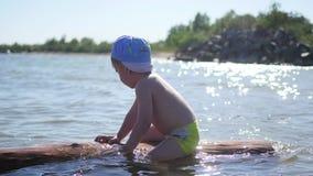 Een gelukkig kind zwemt in het overzees Pret en spelen in openlucht stock video