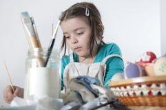 Een gelukkig meisje die paaseieren schilderen Royalty-vrije Stock Afbeeldingen