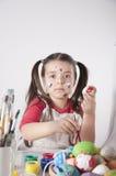 Een gelukkig meisje die paaseieren schilderen stock afbeelding