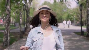 Een gelukkig meisje gaat weg en luistert aan haar moedertaal gebruikend een smartphone stock videobeelden