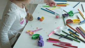 Een gelukkig meisje neemt multicolored plasticine van een container, op de Desktop zijn cijfers en kleurpotloden stock footage