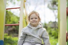 Een gelukkig meisje op de speelplaats beklom op een kinderendia en begon te lachen en te giechelen stock foto