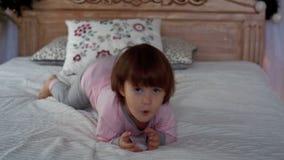 Een gelukkig meisje in pyjama's die op bed liggen stock footage