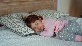 Een gelukkig meisje in pyjama's die op bed liggen stock video