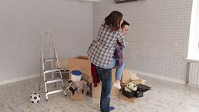 Een gelukkig meisje springt op de rug van haar vrolijke kerel in een nieuwe flat Nieuw huis stock video