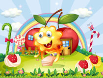 Een gelukkig monster bij de heuveltop met reuzelollys en appel ho Stock Afbeelding