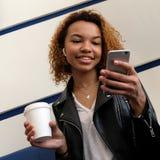 Een gelukkig mooi Afrikaans Amerikaans meisje met een witte draadloze oortelefoon in haar oor onderzoekt de telefoon terwijl het  stock fotografie