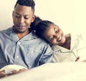 Een gelukkig paar die mobiele telefoons in bed met behulp van stock foto