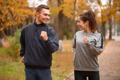 Een gelukkig paar die, die op de straat lopen en bij elkaar glimlachen In het de herfstpark stock fotografie