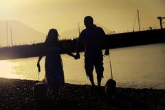 Een gelukkig paar neemt hun hond voor een gang op het strand stock foto's
