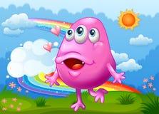 Een gelukkig roze monster die bij de heuveltop met een regenboog in Th dansen Stock Afbeeldingen