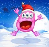 Een gelukkig roze monster die met een rode hoed springen Stock Foto