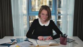 Een gelukkig schoolmeisje leest een boek Bekijkt de camera en glimlacht stock videobeelden