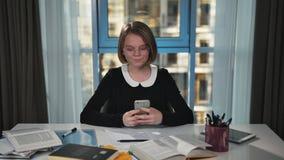 Een gelukkig schoolmeisje schrijft een bericht in het sociale netwerk Gebruikt een smartphone Hij glimlacht stock footage