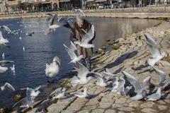 Een gelukkige 83 éénjarigendame met vogels bij de haven van Ohrid-Meer, Macedonië stock fotografie
