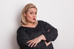 Een gelukkige aantrekkelijke te zware vrouw in studio het pruilen lippen royalty-vrije stock afbeelding