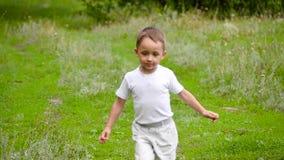 Een gelukkige baby loopt op het groene gras in dichte nabijheid aan het bos stock videobeelden
