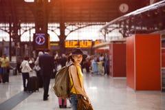 Een gelukkige backpackervrouw die gaan reizen, zich bevindt in het station die aan de trein wachten stock afbeelding