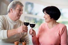 Een gelukkige bejaarde paar het vieren het levensgebeurtenis samen met wijn Royalty-vrije Stock Afbeeldingen