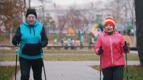 Een gelukkige elderyvrouw geeft handsignaal en twee bejaarden begint op stokken te lopen van het noordse lopen stock video