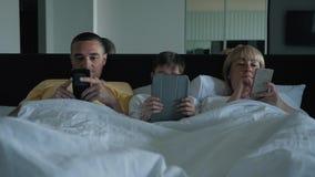 Een gelukkige familie Familiemamma, papa en hun zoon die in bed liggen die op een video letten, babbelend met vrienden en verwant stock video