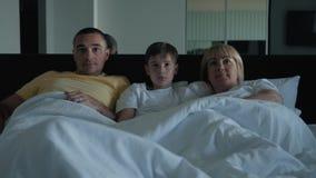 Een gelukkige familie Familiemamma, papa en hun zoon die in bed liggen die op een video letten, babbelend met vrienden en verwant stock videobeelden