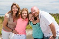 Een gelukkige familie huddles samen met gelukkige glimlachen Stock Foto's