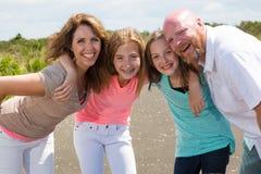 Een gelukkige familie huddles samen met gelukkige glimlachen Royalty-vrije Stock Afbeelding