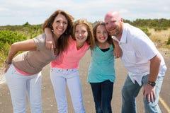 Een gelukkige familie huddles samen met gelukkige glimlachen Royalty-vrije Stock Foto's