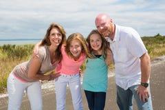Een gelukkige familie huddles samen met gelukkige glimlachen Stock Afbeelding