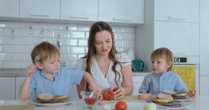 Een gelukkige familie is een jonge mooie moeder in een witte kleding met twee zonen die in blauwe overhemden een witte keuken voo stock video
