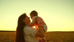 Een gelukkige familie, mamma die met haar weinig dochter in park in de zomer in stralen van zonsondergang spelen Langzame Motie G stock videobeelden