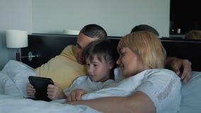 Een gelukkige familie met één kind die op het bed liggen en een digitale tablet gebruiken en smartphones Moderne technologieën va stock footage
