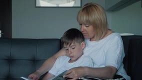 Een gelukkige familie Mum en de zoon lezen een boek stock footage
