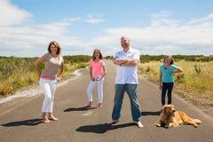 Een gelukkige familie op een stille landweg Stock Foto's