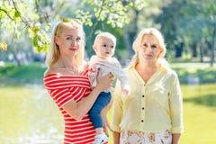 Een gelukkige familie van drie generaties, moeder, dochter, grootmoeder en weinig babykleindochter, verenigt zich op bri stock fotografie