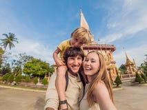 Een gelukkige familie van toeristen op de achtergrond van Wat Chalong in Thailand Het reizen met kinderenconcept stock afbeeldingen