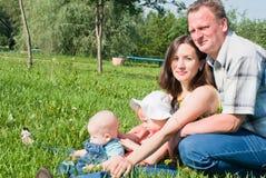 Een gelukkige familie van vier mensen op het gazon Stock Fotografie