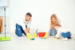 Een gelukkige familie wast de vloer stock afbeeldingen