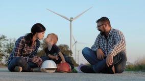 Een gelukkige familie zit op een weg Een kind speelt met aannemershelmen, kust moeder en hoog-fives-hoogtevader stock footage